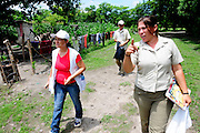 Community health workers walk through the village of Ciudad Romero visiting families to encourage participation in the 'Nefrolempa' health project a series of medical investigations carried out by the 'health team into the high incidence of chronic renal failure in the region.<br /> <br /> Community of Ciudad Romero, Bajo Lempa, El Salvador. 2011.<br /> The 'Nefrolempa' research project is a collaboration between the El Salvador Ministry of Health, the Nephrology Institute of Cuba's Ministry for Public Health and the United Bajo Lempa Committee Association. The aim of the project is to investigate the reasons for the high levels of Chronic Kidney Disease (CKD) suffered by the communities within the Bajo Lempa region. It is exploring whether the use of agrochemicals might be a factor in the prevalence of the disease.<br /> Medical team:.Dr Elsy Brizuela de Jimenez, Directora Unidad de Salud.Miriam Colindres, Nurse.Maria Eraida Velasquez, clinic and laboratory worker..Ecuilia Castro Peraza, Nutritionist.Veronica Contreras, Education for health.Guadelupe Nunez, Psychologist.Luis Diaz General support worker.Dr Raul Herrera Valdes, Nefrologo, Cuba.Dr Miguel Almaguer Lopez, Nefrologo Cuba.Dr Carlos Orantes, Salvadorean Nefrologist.Dr Juan Carlos Awaya, Salvadorean Nefrologist.