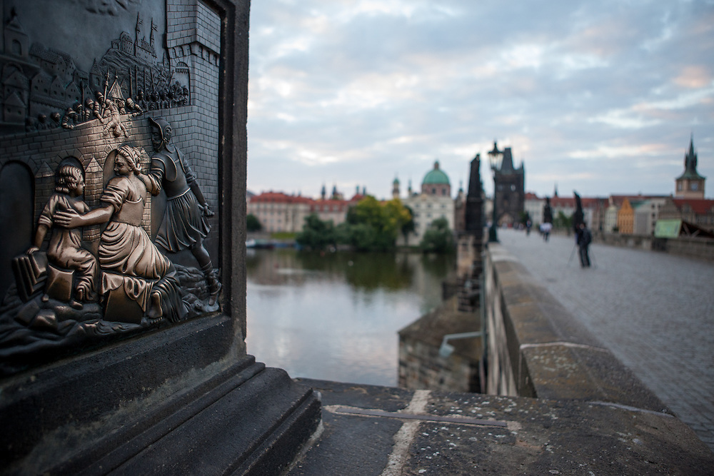 Charles Bridge and the view to Prague Old Town during the early morning change from night to day. St. John of Nepomuk Statue. Touching the statue is a Prague ritual. It is supposed to bring good luck and to ensure that you return to Prague soon.