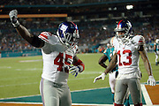 New York Giants wide receiver Odell Beckham (13) smiles as he watches New York Giants tight end Will Tye (45) dance after catching a touchdown pass that ties the score at 17-17 with less than one minute left in the second quarter during the NFL week 14 regular season football game against the Miami Dolphins on Monday, Dec. 14, 2015 in Miami Gardens, Fla. The Giants won the game 31-24. (©Paul Anthony Spinelli)