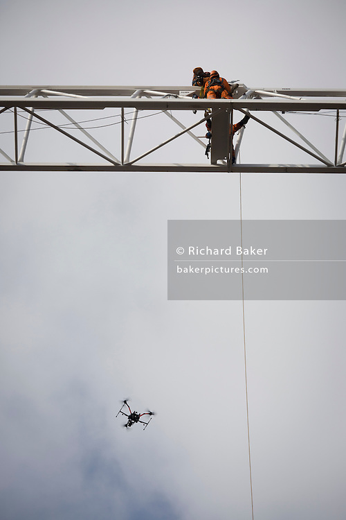 Workmen high on the jib of a crane that will construct the King's College Hospital helipad on Denmark Hill, south London. Watched by a UAV drone that is filming the operation on behalf of the hospital's trust, hovers alongside. King's is home to the largest Major Trauma Centre in the South of England. It is also the 'hub' for the South East London, Kent and Medway (SELKaM) major trauma network, which covers 5.5 million people, or 7.8% of the UK population. The trauma team at King's regularly feature in the Channel 4 documentary series '24 Hours in A&E', which is filmed at the hospital.