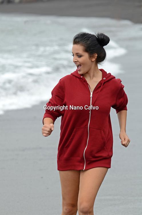 Cute brunette teenager running on the beach