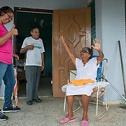 Punta Santiago, PR--Yvonne Ortiz, left, a community organizer with P.E.C.E.S. comforts Armancio Acosta Rivera and his mothe, Dora Sanchez in their home in Punta Santiago, PR, November 8, 2017. Much of Mr. Rivera's home was damaged during the Hurricane Maria which hit the island September 20, 2017. Nearly two months after the storm, his home has no running water or electricity. Mr. Rivera has left the mud and the once-soaked furniture and clothes in his home untouched, waiting for FEMA to come and document the damage. He has been told that he has to leave the evidence of his lost in place in order to receive support to repair his home.  P.E.C.E.S. has provided critical rescue and relief servises for 10 coastal communities in Puerto Rico, supported by the Puerto Rico Recovery Fund.  Photo by Lori Waselchuk/braf.org
