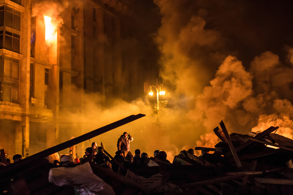 KIEV, UKRAINE - FEBRUARY 19: Anti-government protesters guard the perimeter of Independence Square, known as Maidan, as the Trade Unions Building burns on February 19, 2014 in Kiev, Ukraine. After several weeks of calm, violence has again flared between police and anti-government protesters, who are calling for the ouster of President Viktor Yanukovych over corruption and an abandoned trade agreement with the European Union. (Photo by Brendan Hoffman/Getty Images) *** Local Caption ***