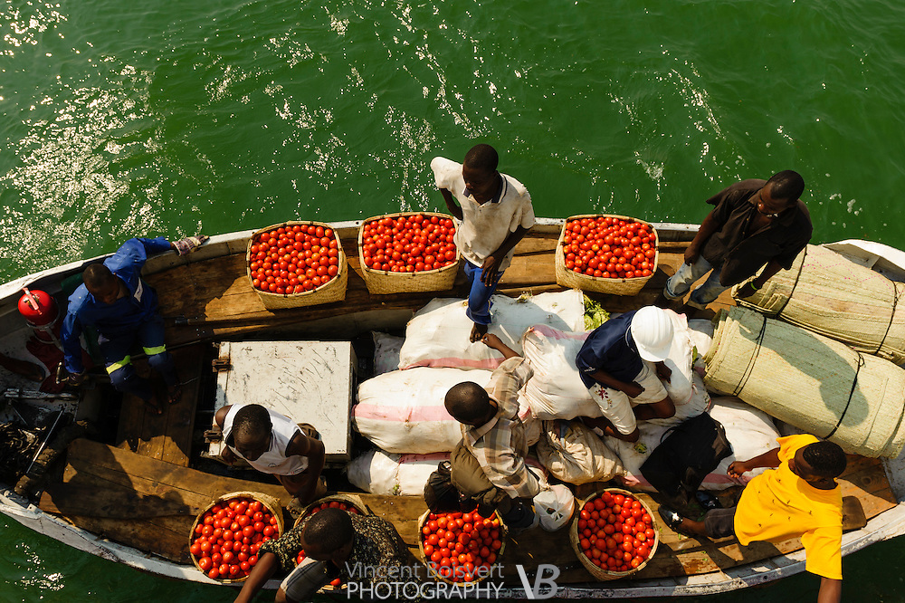 a colorful view of men in a small boat loading their merchandise in the Ilala ferry, malawi