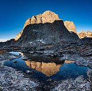 "Near Jackass Pass, War Bonnet Peak catches sunrise light, in Cirque of the Towers, Bridger Wilderness, Wind River Range, Bridger-Teton National Forest, Rocky Mountains, Wyoming, USA. We backpacked to Big Sandy Lake Campground (11 miles round trip with 1000 feet gain). Two hours before sunrise, I departed from Big Sandy Lake to reach Jackass Pass viewpoint for Cirque of the Towers and Lonesome Lake (6.5 miles round trip, 1860 ft gain) on the Continental Divide Trail. The Continental Divide follows the crest of the ""Winds"". Mostly composed of granite batholiths formed deep within the earth over 1 billion years ago, the Wind River Range is one of the oldest mountain ranges in North America. These granite monoliths were uplifted, exposed by erosion, then carved by glaciers 500,000 years ago to form cirques and U-shaped valleys. This image was stitched from multiple overlapping photos."