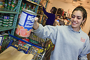 23 DECEMBER 2008 -- CHANDLER, AZ:  Renee Yousif (CQ) a volunteer from Seton Catholic School packs grocery carts for clients of the food bank at the Chandler Christian Community Center in Chandler Tuesday.    PHOTO BY JACK KURTZ