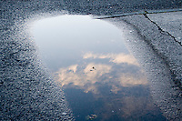 Clouds reflected in puddle on pavement after the rain in Dublin Ireland