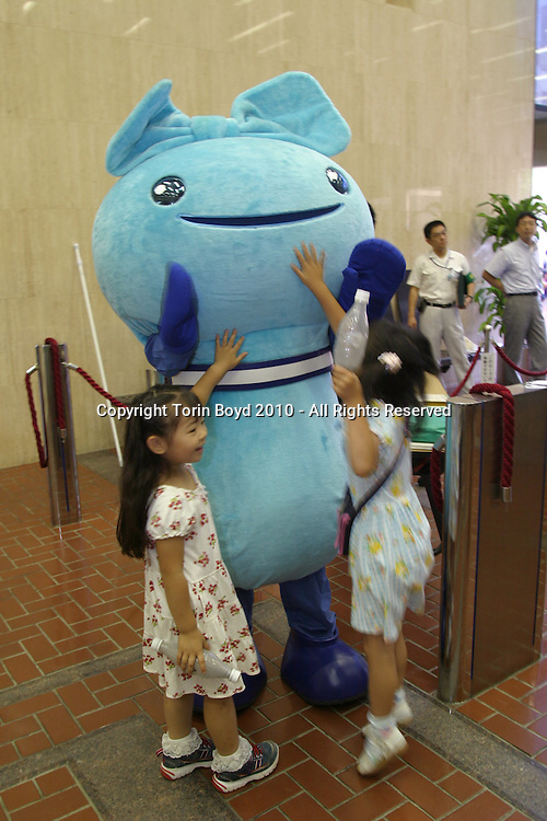"""This is Mio-chan, the official mascot for the city of Yokohama's waste reduction campaign called """"G30"""". This campaign aims to reduce waste output by 30% through legislation and teaching residents to reduce on consumption as well as reuse and recycle items. The annual amount of waste Yokohama produced in FY 2001 was 1.61 million tons, but the city plans to reduce this amount to 1.13. millions tons by FY 2010. This mascot, which is fashioned after a plastic garbage bag symbolizes reduction with its large head shrinking into a smaller body. It is used in promotional events for the G30 campaign as well as on pamphlets and promotion items. In Japanese """"Mio"""" means 30, and """"chan"""" is a cute honorific suffix. Yokohama also designed a special logo for this waste campaign and commissioned an official theme song called """"Ii-ne Yokohama G30"""". Mio-chan is seen here at public event promoting the G30 campaign at Kannai Hall in Yokohama on July 27, 2005."""