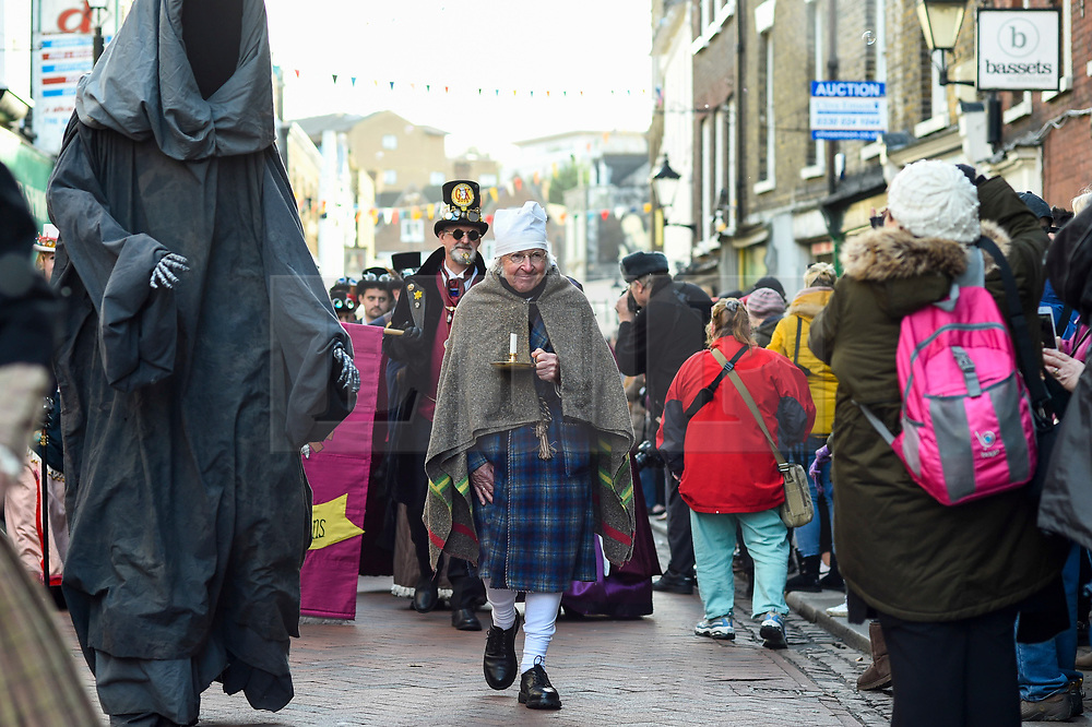 """© Licensed to London News Pictures. 08/12/2019. ROCHESTER, UK. A man dressed as Scrooge, accompanied by a man dressed as Death, both from """"A Christmas Carol"""", take part in the annual Dickensian Christmas Festival in Rochester.  The Kent town is given a Victorian makeover to celebrate the life of the writer Charles Dickens (who spent much of his life there), with Victorian themed street entertainment, costumed parades and a Christmas market.  Photo credit: Stephen Chung/LNP"""