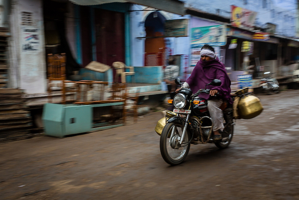 A panning shot of a milkman riding his motorbike through the main street of Old Bundi. Milkmen are ubiquitous in the Bundi mornings, selling milk door to door.