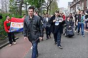 Nederland, Nijmegen, 5-4-2014Demonstratie ter ondersteuning van Geert Wilders en ter veroordeling van de aangifte van burgemeester Bruls, de Nijmeegse wethouders namens de Nijmeegse gemeenteraad. De stoet loopt onder zware politiebegeleiding door de stad naar het politiebureau. Op het spandoek, de nederlandse vlag, staat: geen racist maar realist. Organisator Angelo van den Bos heeft een print met foto's van hem en gekleurde mensen om te bewijzen dat hij ook vrienden heeft onder deze bevolkingsgroep.Foto: Flip Franssen