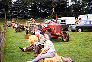 Spectators sitting on straw bales at agricultural show Llansantffraed-Cwmdeuddwr, Rhayader, mid Wales in 1964