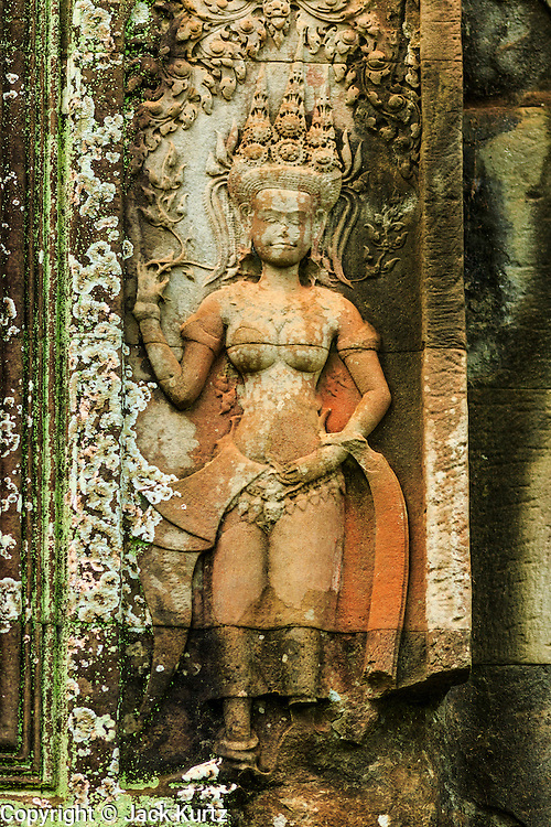 """01 JULY 2013 - ANGKOR WAT, SIEM REAP, SIEM REAP, CAMBODIA:  A bas relief of an Aspara dancer in Angkor Wat. Angkor Wat is the largest temple complex in the world. The temple was built by the Khmer King Suryavarman II in the early 12th century in Yasodharapura (present-day Angkor), the capital of the Khmer Empire, as his state temple and eventual mausoleum. Angkor Wat was dedicated to Vishnu. It is the best-preserved temple at the site, and has remained a religious centre since its foundation– first Hindu, then Buddhist. The temple is at the top of the high classical style of Khmer architecture. It is a symbol of Cambodia, appearing on the national flag, and it is the country's prime attraction for visitors. The temple is admired for the architecture, the extensive bas-reliefs, and for the numerous devatas adorning its walls. The modern name, Angkor Wat, means """"Temple City"""" or """"City of Temples"""" in Khmer; Angkor, meaning """"city"""" or """"capital city"""", is a vernacular form of the word nokor, which comes from the Sanskrit word nagara. Wat is the Khmer word for """"temple grounds"""", derived from the Pali word """"vatta."""" Prior to this time the temple was known as Preah Pisnulok, after the posthumous title of its founder. It is also the name of complex of temples, which includes Bayon and Preah Khan, in the vicinity. It is by far the most visited tourist attraction in Cambodia. More than half of all tourists to Cambodia visit Angkor.      PHOTO BY JACK KURTZ"""