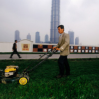 Swapping plough for lawn mower, a migrant at work by the skyscrapers of Pudong, the city's new financial district. The jacket still bears its sleeve label - a sign of style...From China [sur]real © Mark Henley..