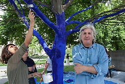© licensed to London News Pictures. London, UK 25/06/2013. Artist of 'The Blue Trees' Konstantin Dimopoulos helping Trees for Cities charity and the City of London to create 'The Blue Trees' environmental art installation at Festival Gardens, next to St Paul's Cathedral as part of the annual City of London Festival. Trees in Festival Gardens being coloured 'blue' using a tree safe colourant.  By colouring the trees blue, Trees for Cities want people to stop and 'notice' the trees, which are so often taken for granted. The installation will raise awareness of the significant decline of our city trees over the last decade, and the threats they face from climate change, pests and diseases. Photo credit: Tolga Akmen/LNP