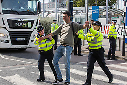 London, UK. 5 September, 2019. Metropolitan Police officers remove an activist from the road in front of a truck outside ExCel London on the fourth day of a week-long carnival of resistance against DSEI, the world's largest arms fair.
