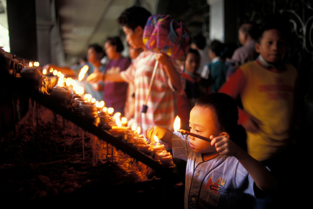 Philippines, Cebu Island, Boy lights devotional candles at Basilica del Santo Niño in Cebu City