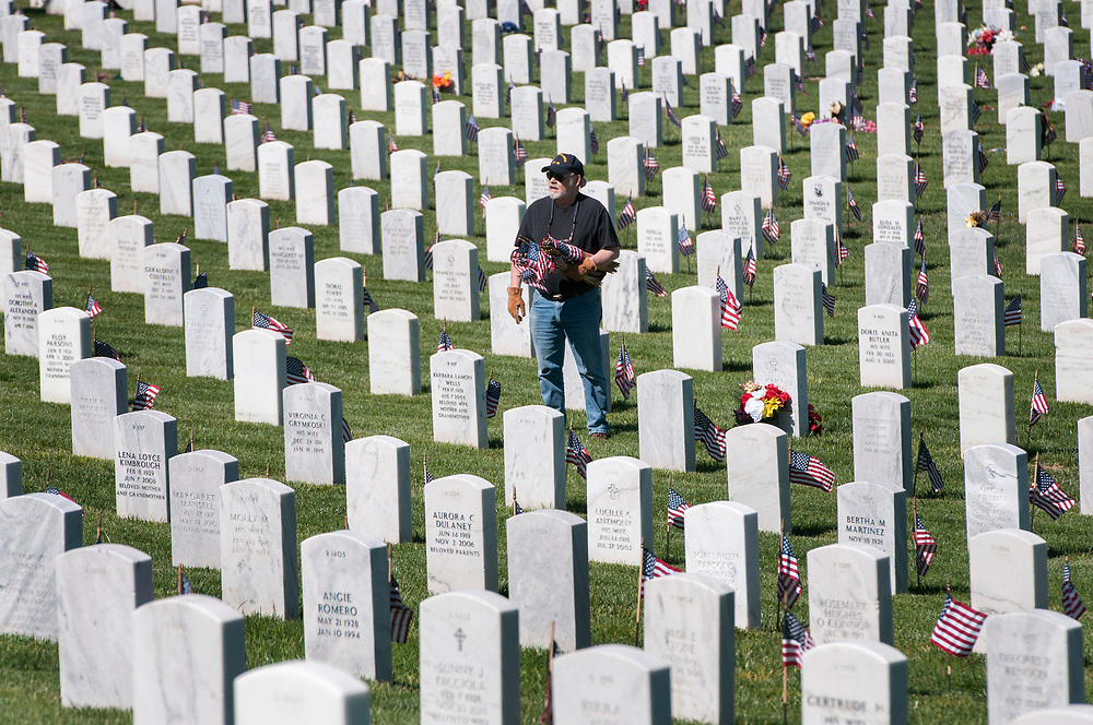 em052617c/a/Charles Green, from Los Alamos, plants flags on graves at the Santa Fe National Cemetery on Friday May 26, 2017. The flags on the over 58,000 graves at the cemetery will be there for the Memorial Day weekend as well as events on Monday. (Eddie Moore/Albuquerque Journal