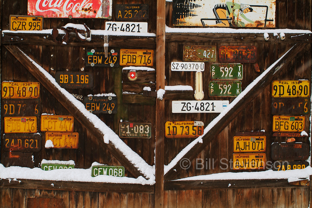 An image of an old garage covered with licence plates with snow in Truckee CA.