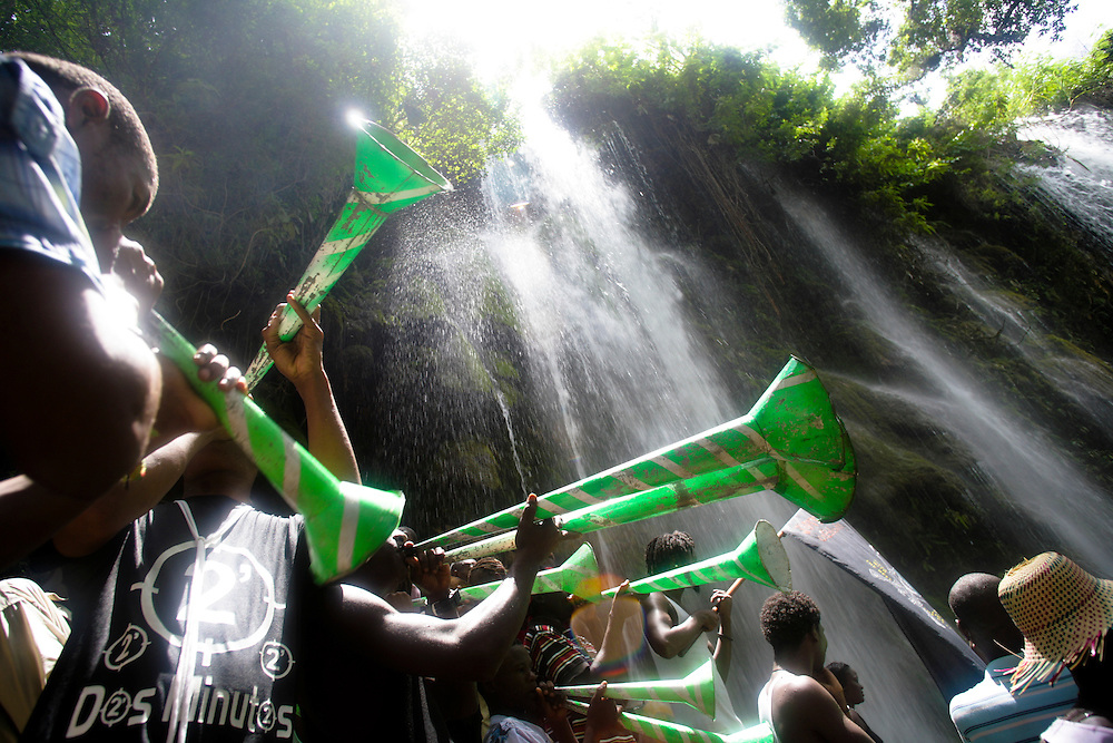 A band plays at the waterfall at Saut d'Eau on July 16th, the anniversary of the 1983 sighting of the Virgin Mary, alternately identified as the Vodou loa, or spirit, of Erzulie Freda, the Goddess of Love..The waterfall at Saut D'Eau is the site of the largest Vodou and Catholic pilgrimage in Haiti. A second sighting of the Virgin was reported during the American occupation. Each year, thousands of Haitian pilgrims make their way to Saut D'Eau to bathe in the sacred water and revel in the presence of the loa, particularly Erzulie and Damballah the Serpent, father of all life and keeper of spiritual wisdom, who is said to live in the falls. The water is believed to be curative and many women come to Saut d'Eau seeking fertility.