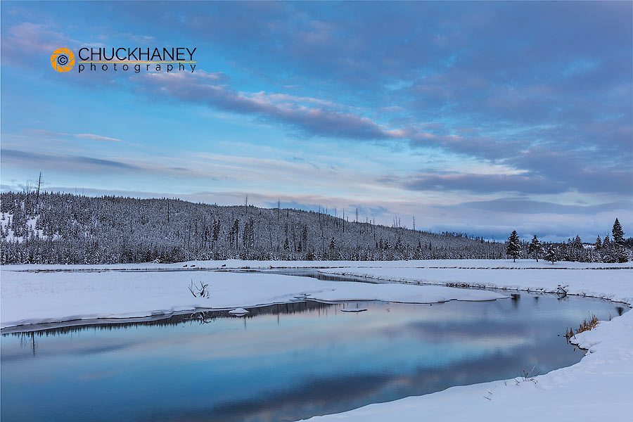 Sunrise clouds reflect inot the Madison River in winter in Yellowstone National Park, Wyoming, USA
