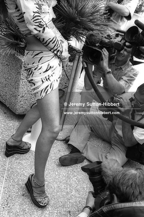 Media television crews film a porn actress at a curtain raising press photo opportunity day for Hot D'Or - the pornography film industry awards events,  during the Cannes Film Festival, at a hotel in Cannes, South of France, in May 1999.