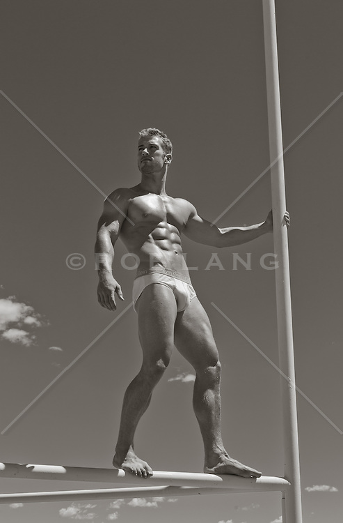 hot guy in his underwear standing on metal poles against the sky