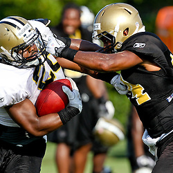 August 6, 2011; Metairie, LA, USA; New Orleans Saints running back Mark Ingram (28) is grabbed by cornerback Leigh Torrence (24) during training camp practice at the New Orleans Saints practice facility. Mandatory Credit: Derick E. Hingle