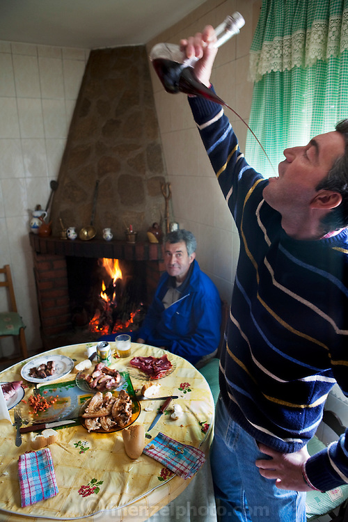 Miguel Angel Martinez Cerrada watches as his brother Paco quenches his thirst with a long pour of red wine from a porron, a traditional glass container designed to eliminate the need for individual glassware at their house in the tiny village of Zarzuela de Jadraque, Spain. (From the book What I Eat: Around the World in 80 Diets.)  Because the brothers eat mainly meat, they're largely self-sufficient when it comes to food. Because there isn't a bakery or market in their small village, they shop once a week in Guadalajara or another larger town about a half-hour drive away.  MODEL RELEASED.