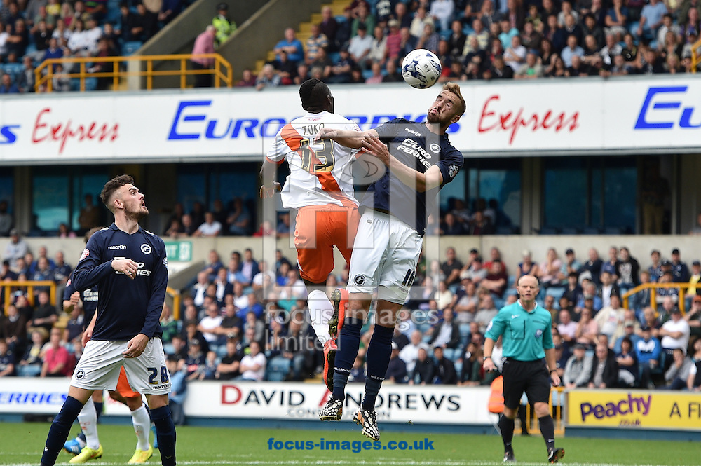Mark Beevers of Millwall heads the ball clear of Francois Zoko of Blackpool during the Sky Bet Championship match at The Den, London<br /> Picture by Alan Stanford/Focus Images Ltd +44 7915 056117<br /> 30/08/2014