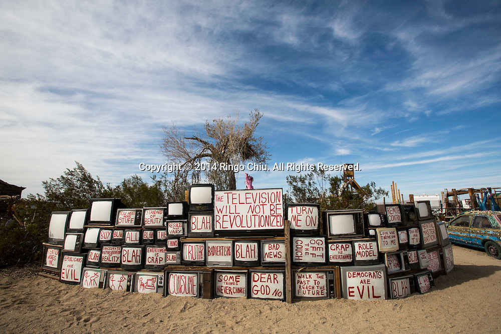 "An art work ""The Revolution Will Not Be Televised"" is displayed at East Jesus, an experimental, habitable, extensible artwork gallery, on  January 4, 2014, in Slab City, California. Slab City or The Slabs is a snowbird campsite in the Colorado Desert in southeastern California, used by recreational vehicle owners and squatters from across North America. It takes its name from the concrete slabs that remain from the abandoned World War II Marine barracks of Camp Dunlap. (Photo by Ringo Chiu/PHOTOFORMULA.com)"