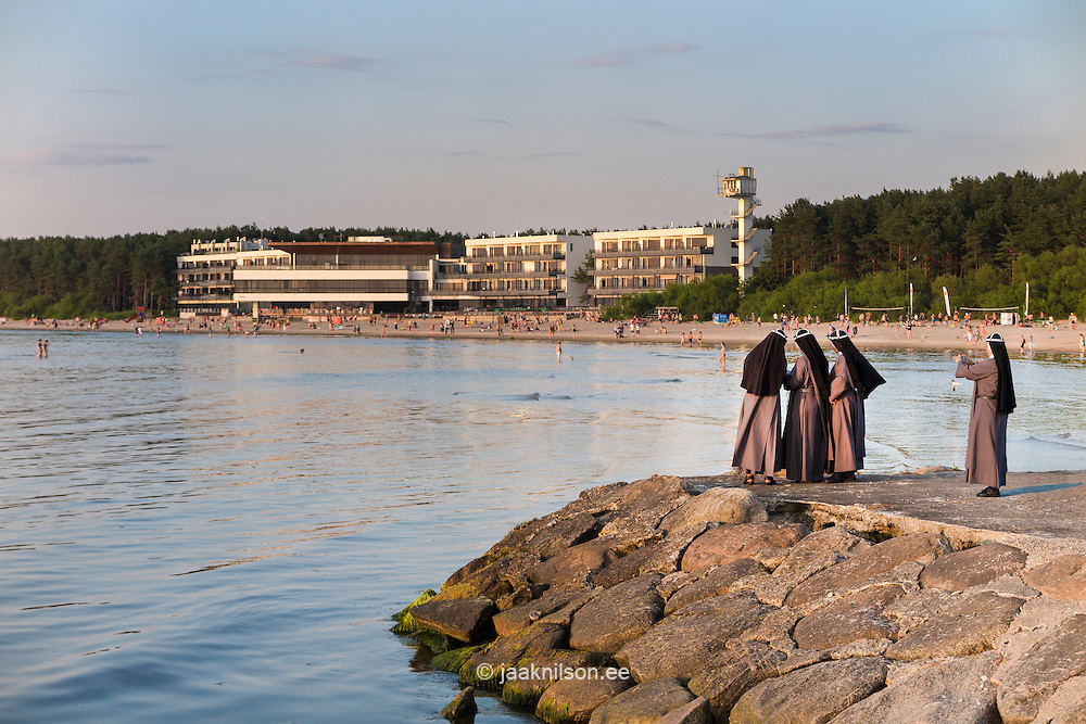 Nun taking photograph of three nuns. Pirita beach in Estonia.