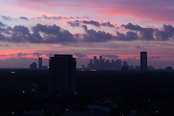 Silhouette of Houston, Texas skyline at sunset from the west.