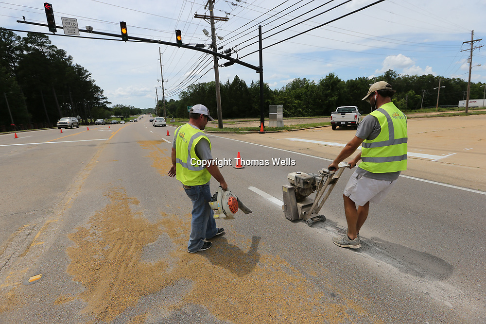 Tupelo Public Works employees Donald Dykes, left, and Jake Logan grind off the old lane markings at the new traffic light on West Main Street at Ballard Park is ready to go active.