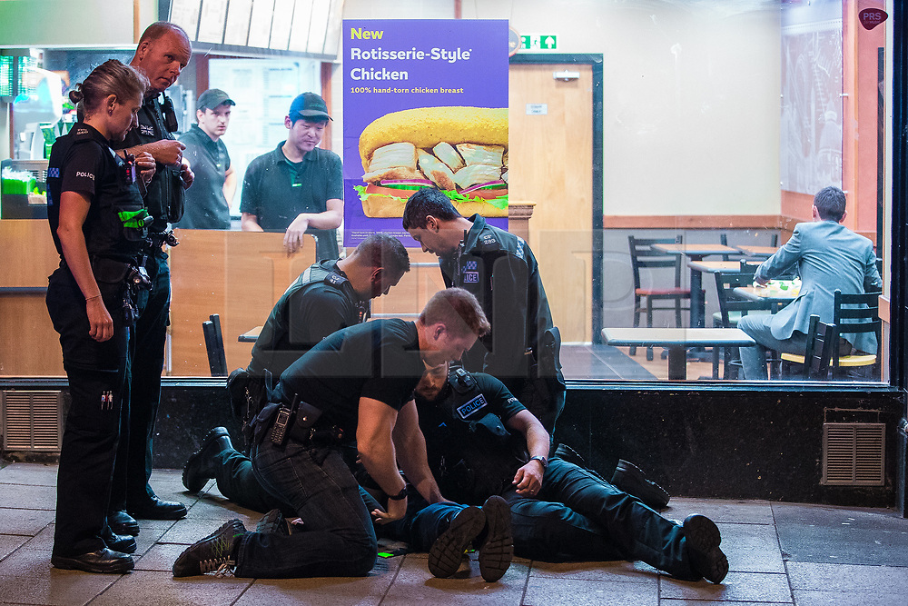 © Licensed to London News Pictures . 26/09/2017. Brighton, UK. Police detain , handcuff , tape up the legs and put a hood over the head of a man outside a branch of Subway , after a fight in Steine Gardens in the Kemptown area of the city . Revellers at the end of a night out in Brighton during Freshers week , when university students traditionally enjoy the bars and clubs during their first nights out in a new city . Photo credit: Joel Goodman/LNP