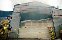 JEROME A. POLLOS/Press..Coeur d'Alene firefighter Jeff Sells prepares to help open an access point to extinguish a fire Friday in a building at Ground Force Manufacturing. The initial damage is estimated at more than $700,000. One employee of Ground Force was taken to the hospital for smoke inhalation.