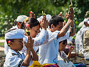 20 JULY 2016 - KUSAMBA, BALI, INDONESIA: Balinese Hindus pray on Kusamba beach during a ceremony Thursday afternoon. Several hundred Balinese Hindus gathered on the beach in Kusamba, Bali, for a ceremony to honor the full moon. They prayed for more than hour and then community leaders threw an offering into the ocean.      PHOTO BY JACK KURTZ