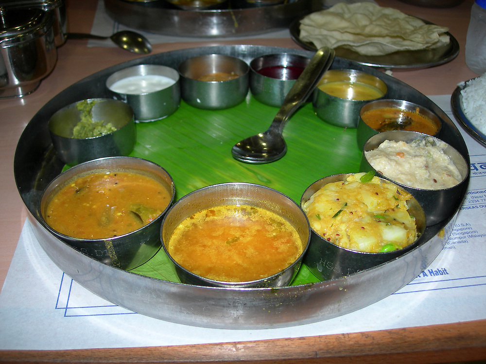 An Indian thali is a selection of different dishes, usually served in small bowls on a round tray. The round tray is generally made with steel with multiple compartments. Typical dishes include rice, dhal, vegetables, roti, papad, curd (yoghurt), small amounts of chutney or pickle, and a sweet dish to top it off.