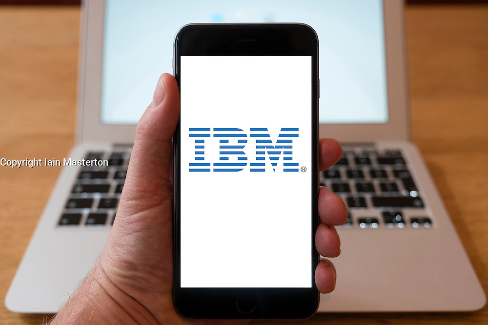 Using iPhone smartphone to display logo of IBM computer hardware and IT company