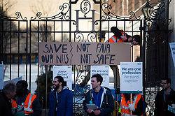 © Licensed to London News Pictures. 12/01/2016. London, UK. A Junior doctor hangs a sign from the hospital gates on the Picket line at St Mary's Hospital in Paddington, West London. Thousand of doctors across England have gone on strike in a dispute with the government over a new contract. Photo credit: Ben Cawthra/LNP