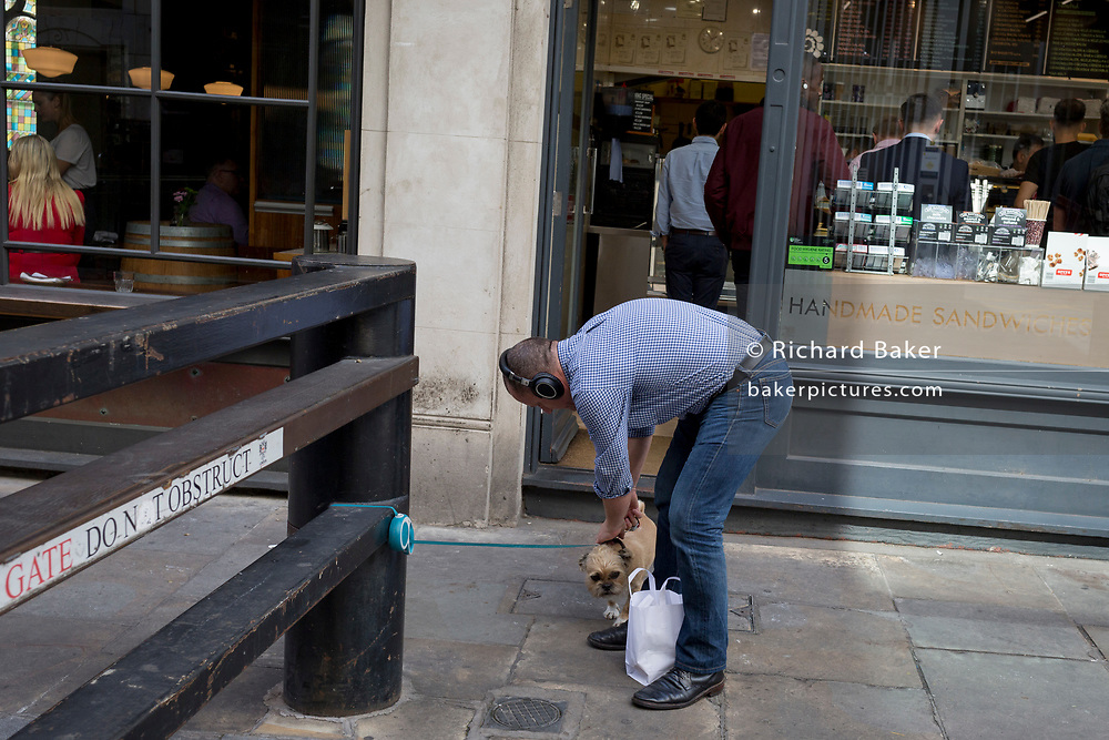 A pet dog is untied again after its owner returns from buying lunch inside a sandwich business during the lunchtime rush on Watling Street, the former Roman thoroughfare, in the City of London, (aka The Square Mile) the capital's financial district, on 3rd September 2019, in London, England.