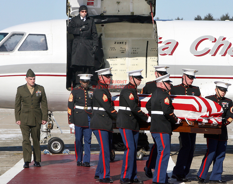 (02/15/07-Bedford,MA) The return of Swampscott Marine Jennifer Harris. The flag draped casket of Marine Captain Jennifer Harris is taken off a plane at Hanscom Airforce base today. ED NOTE Marine Major Christopher Aaby (CQ) , close friend of Jennifer is at far left. He escorted her casket from Dover Airforce base to Hanscom. Staff photo by Mark Garfinkel.