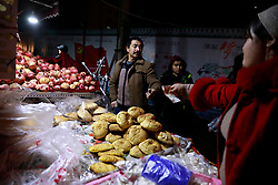 An ethnic Uighur food stall owner tends to a customer in Urumqi city, Xinjiang Uighur Autonomous Province, China, 18 November 2017. Uighurs, a Muslim ethnic minority group in China, make up about 40 per cent of the 21.8 million people in Xinjiang, a vast, ethnically divided region that borders Pakistan, Afghanistan, Kazakhstan, Kyrgyzstan and Mongolia. Other ethnic minorities living in here include the Han Chinese, Kyrgyz, Mongolian and Tajiks people. Xinjiang has long been subjected to separatists unrests and violent terrorist attacks blamed by authorities on Islamist extremism while human rights groups say Chinese repression on religious rights, culture and freedom of movement caused undue tensions. Life however goes on under the watchful eye of the government for the ethnic Uighurs living in the city of Urumqi and surrounding areas and the region is still considered an attractive tourist spot. A recent report by state media Xinhua news agency claims Xinjiang received more than 100 million tourists in 2017, 'the highest figure in its history'.
