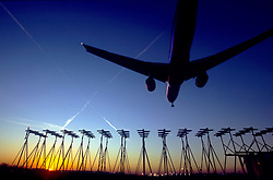 Heathrow Airport, aircraft in silhouette coming in to land at sunrise, November 2005, Ref CHE02658, D.P