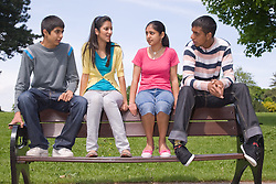 Group of friends sitting on a park bench together,