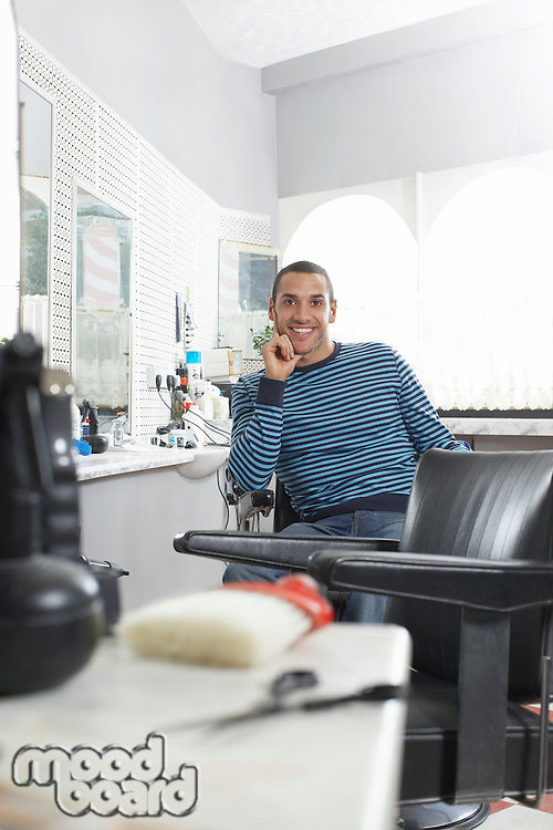 Man sitting in barbers shop smiling portrait