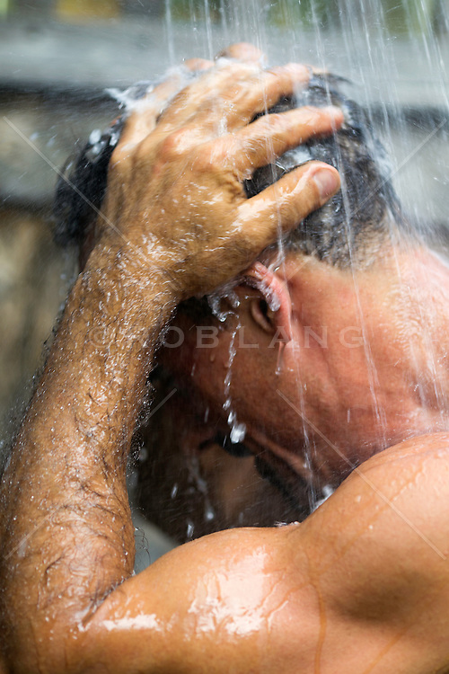 man washing his hair in a shower