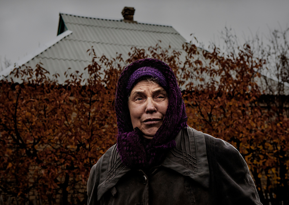 Luhanske, eastern Ukraine, Nov. 2017.<br /> <br /> Lyubov Stepanova, 71.<br /> <br /> With her house and its refurbished roof in the background, she reflects on when the property was hit by three artillery shells in 2015, fired by pro-Russian separatists&rsquo;.<br /> <br /> While fortunate to escape injury herself, several of her neighbours have been killed during the shelling of recent years. <br /> <br /> She and her husband had built up their house over 42 years and the roof was replaced in the spring of 2017 through support from the UNHCR.