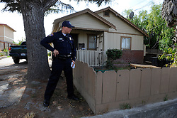 Salinas police officer Richard Lopez takes a protective position as partner Jeffrey Lofton interviews a resident of Fremont Street. The Community Alliance for Safety and Peace is an ambitious program that aims to steer youth away from gang violence and toward solutions offered by more than 30 local organizations offering alternatives.