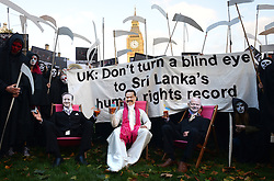 © Licensed to London News Pictures.02/11/2013. London, UK. Amnesty supporters dressed as grim reapers accompanied by Prime Minister David Cameron and Foreign Secretary William Hague lookalikes gather in Parliament Square to protest UK government endorsement of Sri Lanka at next week's Commonwealth Heads of Government Meeting (CHOGM) in Colombo.Photo credit : Peter Kollanyi/LNP